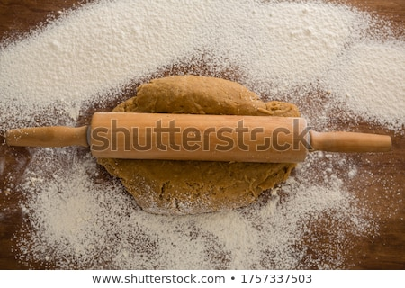 Flattening dough with rolling pin with sprinkled over flour on a wooden table Stock photo © wavebreak_media
