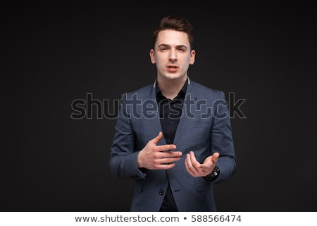 Young attractive businessman in grey jacket, costly watch and black shirt, black background Stock photo © Traimak