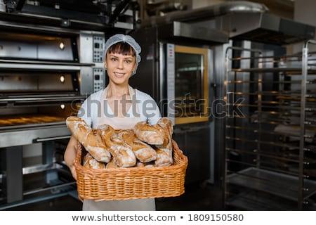 Baker holding basket with bakery products. Stock photo © RAStudio