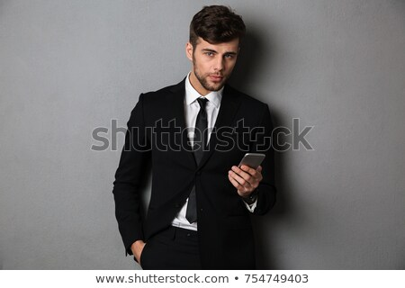 Young confident businnesman with hand in his pocket holding mobi Stock photo © deandrobot