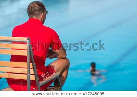Young man sitting at poolside watching woman, rear view Stock photo © IS2