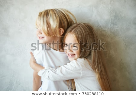 two happy kids sister standing at blank grey wall and embracing stock photo © lopolo