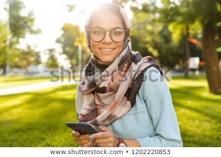 Photo of lovely arabian woman wearing headscarf using mobile pho Stock photo © deandrobot