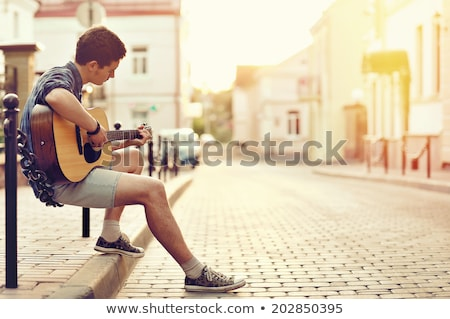 Teen boy playing acoustic guitar stock photo © boggy