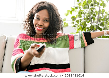 black woman listening tv at home with remote control Stock photo © Lopolo