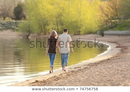 cute young loving couple walking outdoors on the beach stock photo © deandrobot