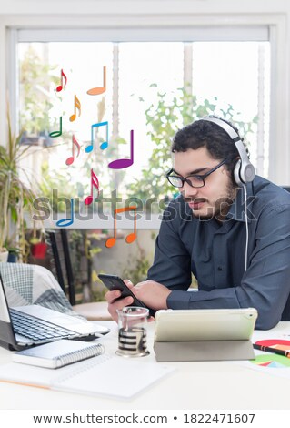 Contemplative businessman working in headphones Stock photo © pressmaster