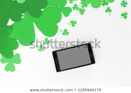 tablet pc and st patricks day decorations on white Stock photo © dolgachov
