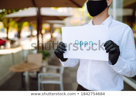 young barista hanging paper notice saying that cafe is open on transparent door stock photo © pressmaster