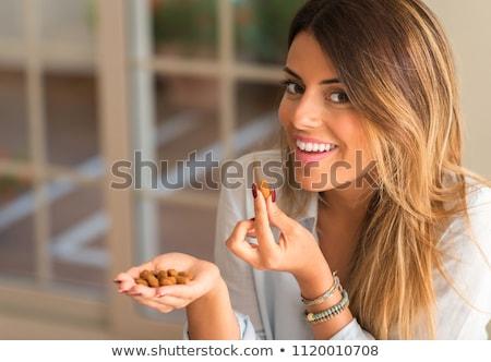 Aantrekkelijke vrouw eten amandelen vrouwelijke persoon glimlachend Stockfoto © HighwayStarz
