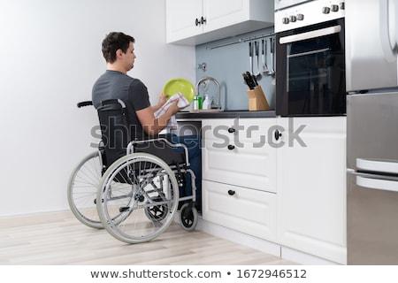 Fogyatékos férfi takarítás edények konyha ül Stock fotó © AndreyPopov
