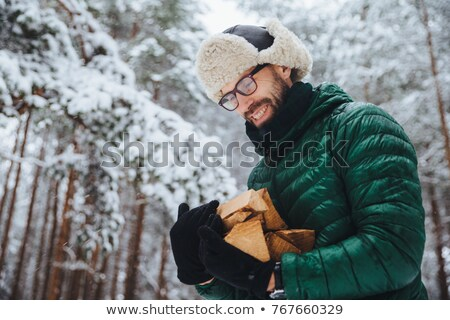 Pleased man in spectacles looks hapily at firewood which he log in winter forest, going to make fire Stock photo © vkstudio
