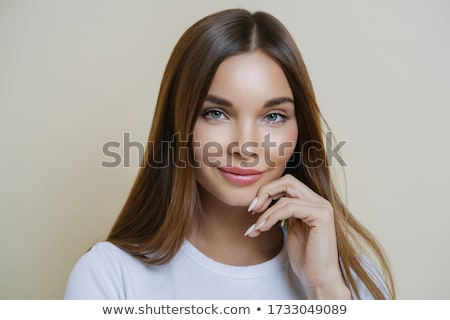 Charming good looking millennial woman keeps hand near face, has healthy glowing skin, dark hair, bl Stock photo © vkstudio