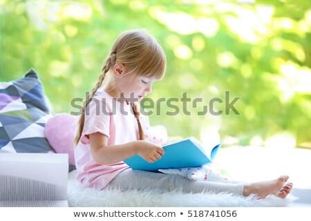 Aranyos kislány olvas könyv otthon ablakpárkány Stock fotó © Illia