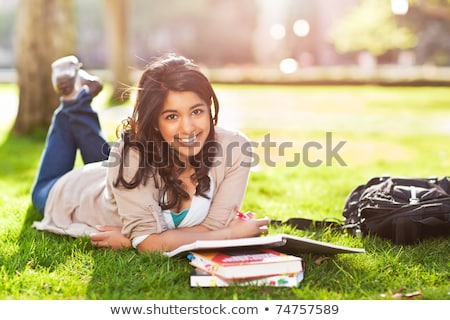 a shot of an caucasian student studying on campus lawn stock photo © hasloo