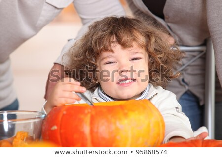 A plump kid carving a pumpkin. Stock photo © photography33
