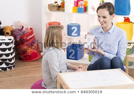 smart girl draws the attention of teacher stock photo © stockyimages