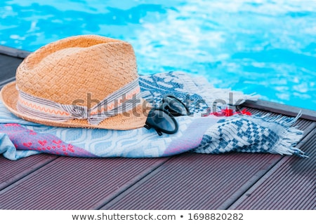 Sun hat and beach towel by swimming pool Stock photo © ABBPhoto