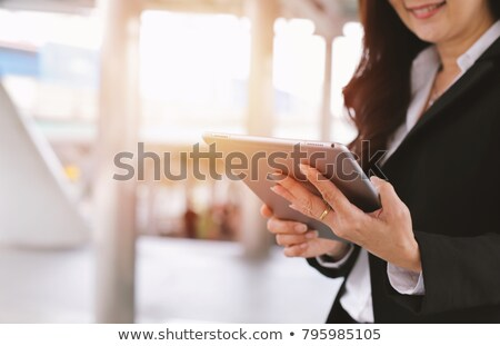 Attractive woman using a tablet outdoors Stock photo © dash