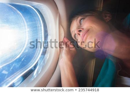 Női repülőgép élvezi kilátás fülke ablak Stock fotó © sarymsakov