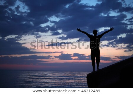 Silhouette guy placed hands in sides on breakwater in evening ne Stock photo © Paha_L