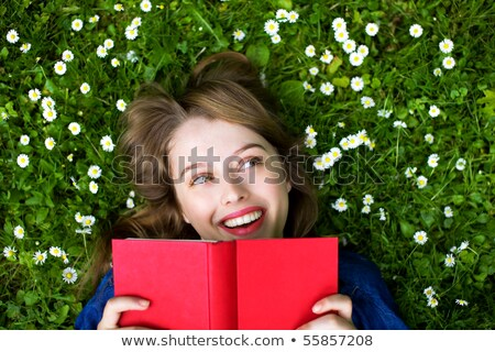 happy young people reading books on lawn outdoors stock photo © deandrobot