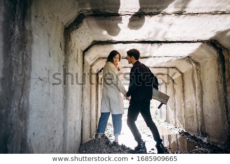 Couple in love walking together through a railway tunnel Stock photo © adamr