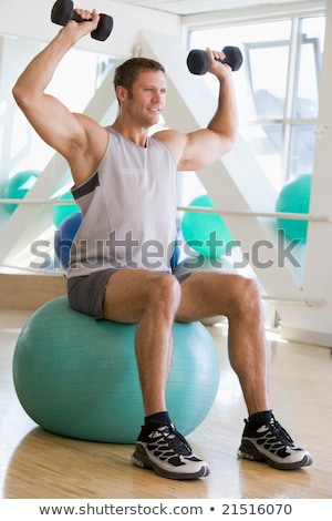 Man Using Hand Weights On Swiss Ball At Gym stock photo © monkey_business