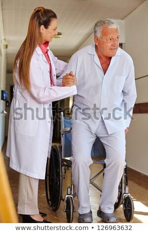 Сток-фото: �едсестра · толкает · пожилую · женщину · в · инвалидной · коляске · вниз · по · больнице · C