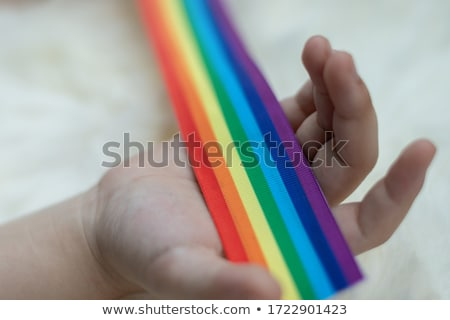 hands holding rainbow gay pride awareness ribbon Stock photo © dolgachov