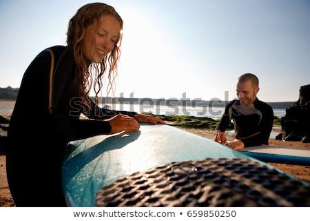 Pár gyantázás szörfdeszkák mosolyog tengerpart víz Stock fotó © IS2