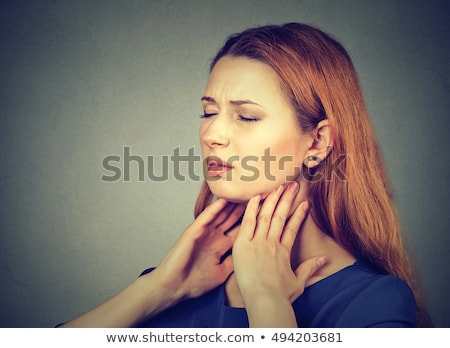 Closeup girl with sore throat touching her neck. On gray wall ba Stock photo © eddows_arunothai