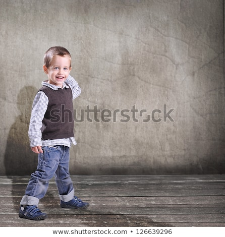 portrait of adorable smilling little boy standing in studio on grey background stock photo © traimak