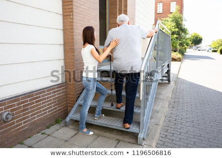 Daughter Assisting Her Father Climbing Staircase Stock photo © AndreyPopov