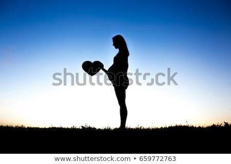 беременная женщина Touch живота сидеть землю свет Сток-фото © Lopolo
