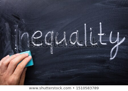 Person's Hand Erasing In Text From Inequality Word Stock photo © AndreyPopov
