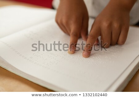 Close-up of blind mixed-race schoolboy hands reading a braille book in classroom at elementary schoo Stock photo © wavebreak_media