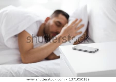 smartphone on bedside table near sleeping man Stock photo © dolgachov