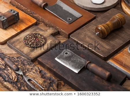 Different sizes and shapes kitchen chopping boards on wooden background with meat hatchets, fork and Stock photo © DenisMArt