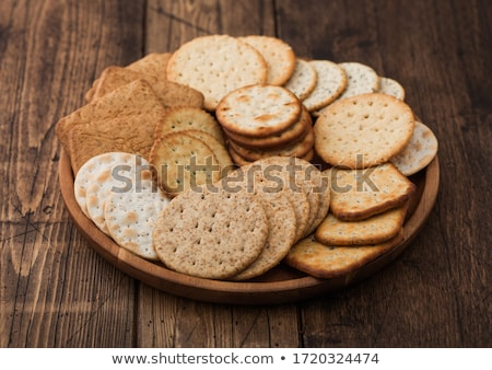 Various organic crispy wheat, rye and corn flatbread crackers with sesame and salt in round plate on Stock photo © DenisMArt