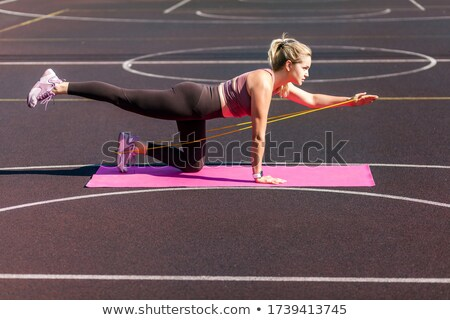 Image of concentrated woman doing workout with expander equipment Stock photo © deandrobot