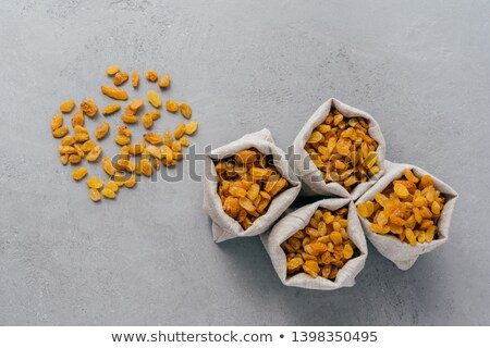 Sweet dry raisins in hessian sacks isolated over grey background. Copy space. Tasty dried fruit for  Stock photo © vkstudio
