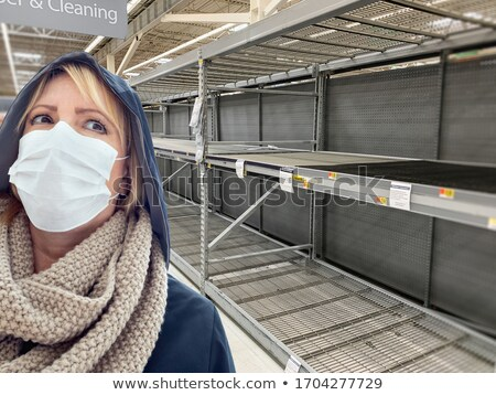 Young Woman Wearing Medical Face Mask In Empty Aisle of Grocery  Stock photo © feverpitch