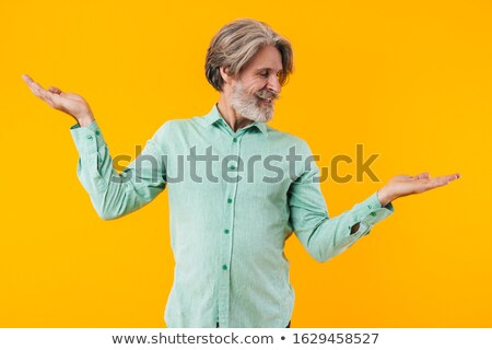 Cheery elderly grey-haired bearded man showing copyspace. Stock photo © deandrobot