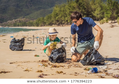 Dad and son in gloves cleaning up the beach pick up plastic bags that pollute sea. Natural education Stock photo © galitskaya