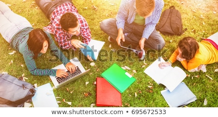 Stock photo: College students using laptop on campus lawn