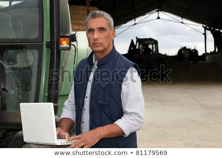 Farmer with laptop stood by tractor Stock photo © photography33