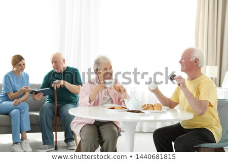 senior woman having breakfast with home care in the background Stock photo © photography33