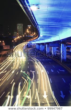 Circular viaduct road rainbow light trails night scene Stock photo © Artphoto