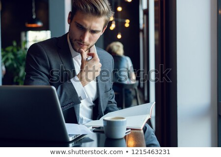 Stock photo: Businessman having a coffee at his desk